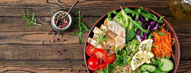 Bouddha bol déjeuner avec du poulet grillé et du quinoa, tomates, guacamole et roquette. top vie