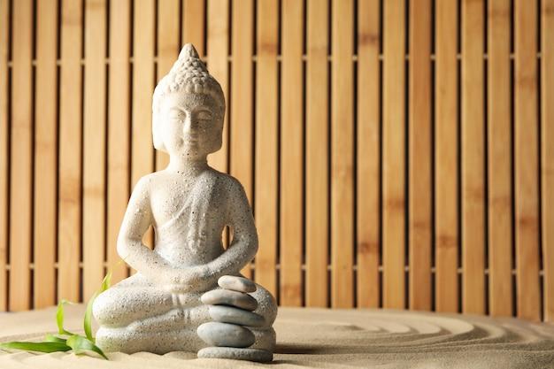 Bouddha et feuille sur fond de sable. concept zen