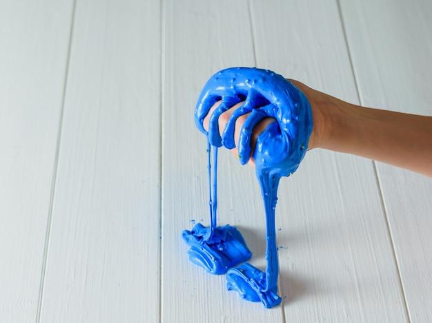 La boue bleue s'écoule de la main droite de l'enfant sur la table blanche.