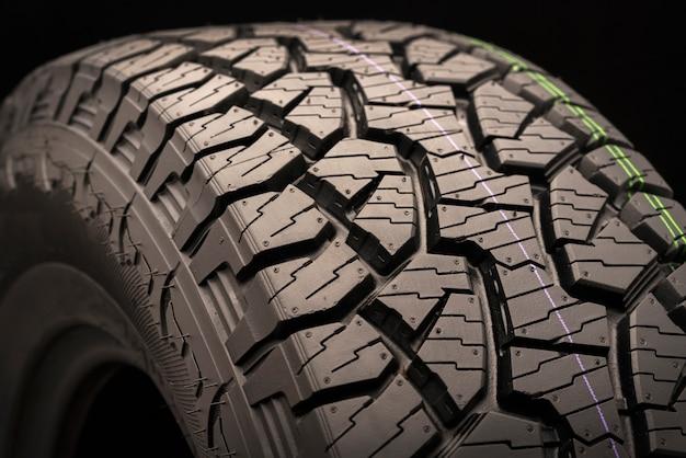 Boue tous les pneus tout-terrain pour suv sur un gros plan de fond noir, l'accent sur la bande de roulement.