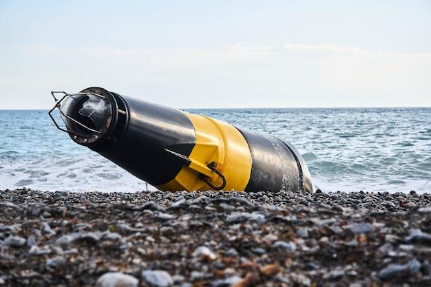 Bouée de mer noire et jaune endommagée (marque de danger cardinal) échouée à terre après une tempête
