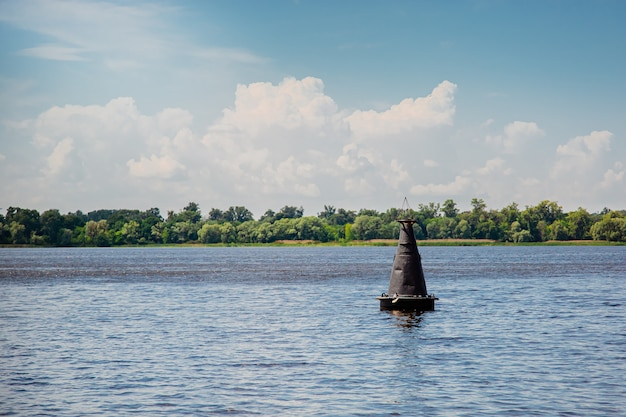 Une bouée noire sur une surface d'eau calme. panneau d'avertissement sur l'eau par une journée ensoleillée.