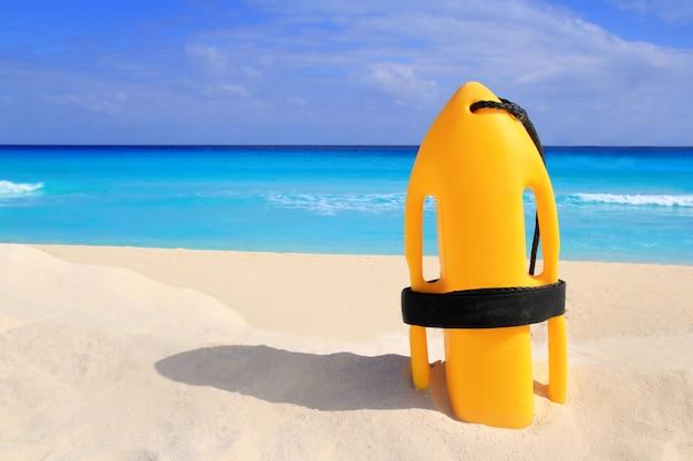 Bouée de sauvetage baywatch jaune sur une plage tropicale