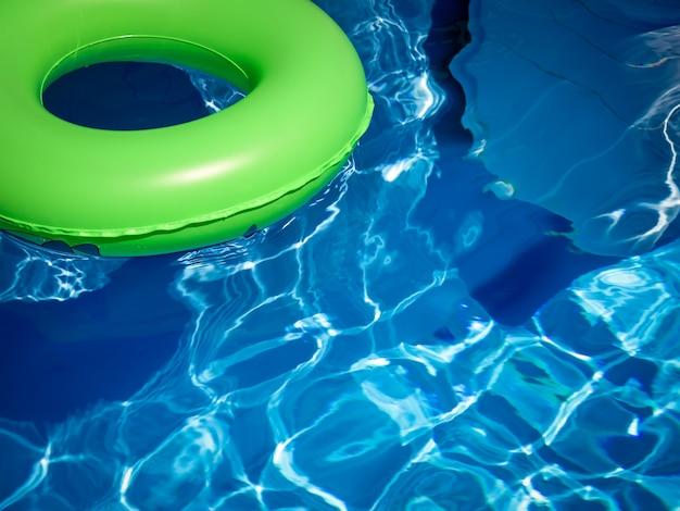 Bouée de sauvetage de couleur vert vif flottant sur l'eau turquoise bleue