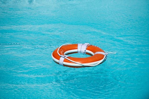 Bouée de sauvetage dans la piscine concept de vacances d'été bouée de sauvetage dans le concept d'aide à l'eau