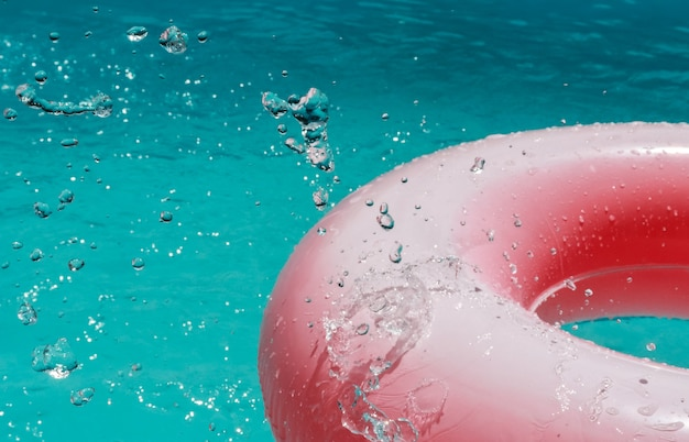 Bouée de sauvetage gonflable cercle rose avec éclaboussures d'eau dans la piscine en gros plan