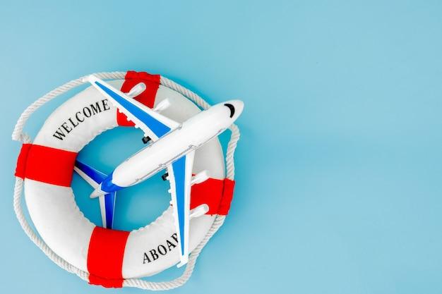 Bouée de sauvetage et modèle d'avion sur fond bleu. concept d'été ou de vacances. espace de copie.