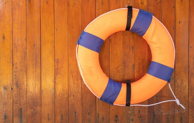 Bouée de sauvetage en mousse orange sur un mur en bois