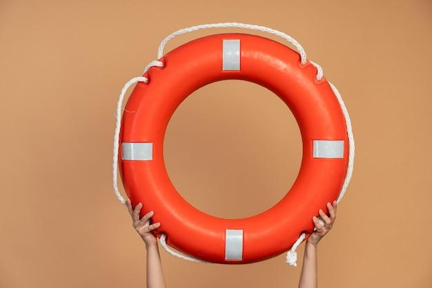 Bouée de sauvetage orange main dans la main. bouée de sauvetage sur fond orange