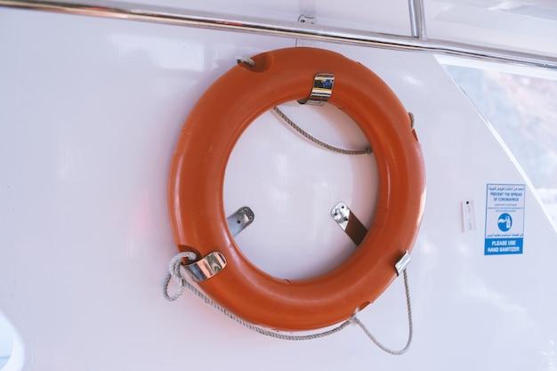 Bouée de sauvetage orange pour la sécurité en mer attachée au bateau de croisière sur fond blanc