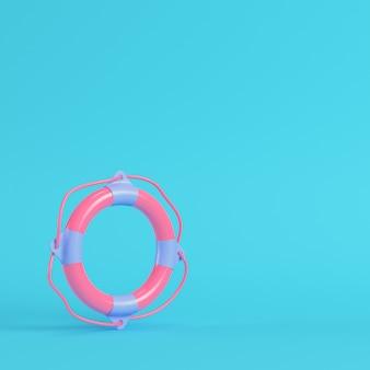 Bouée de sauvetage rose sur fond bleu vif dans des couleurs pastel