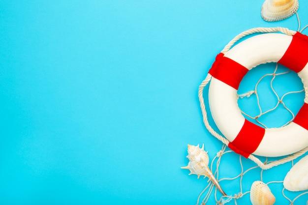 Bouée de sauvetage rouge-blanc avec coquillages sur fond bleu