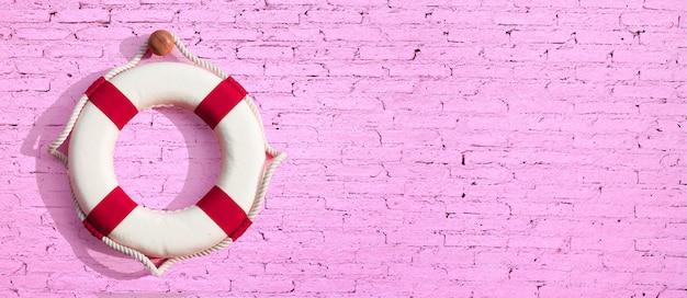 Bouée de sauvetage sur la surface du mur de brique rose