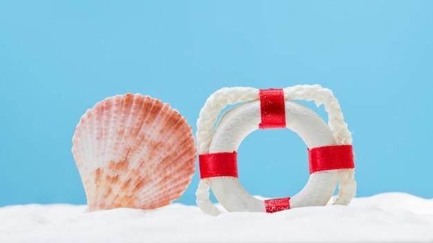 Bouée de vie et coquillage sur sable blanc. concept d'été