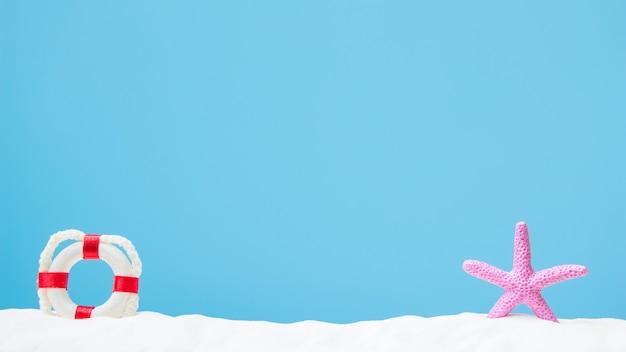 Bouée de vie et étoile de mer de couleur rose sur sable blanc. concept d'été
