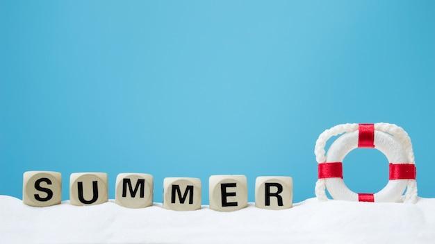 Bouée de vie et texte d'été sur le sable blanc. concept d'été