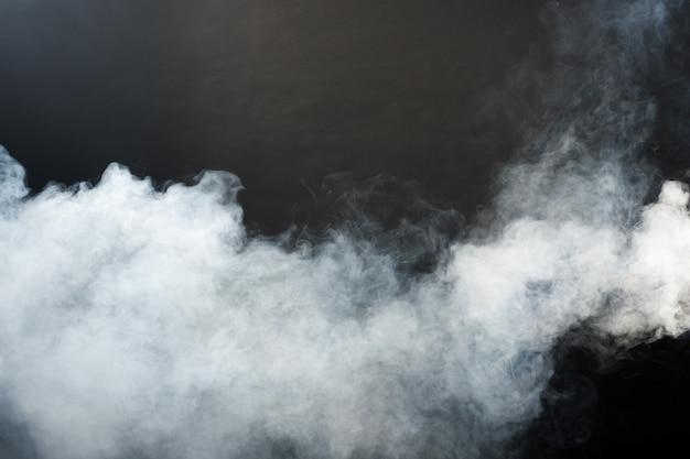 Bouffées denses et moelleuses de fumée blanche et de brouillard sur fond noir, nuages de fumée abstraits, mouvement flou et flou. fumer des coups de glace carbonique de la machine et voleter dans l'air, effet de texture