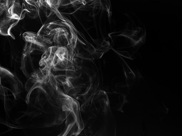 Bouffées moelleuses de fumée blanche et de brouillard sur fond noir, concept de feu et d'obscurité