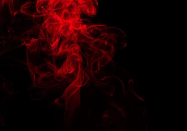 Bouffées moelleuses de fumée rouge et de brouillard sur fond noir, concept de feu et d'obscurité