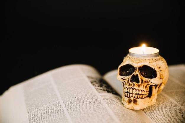 Bougeoir à crâne et livre ouvert