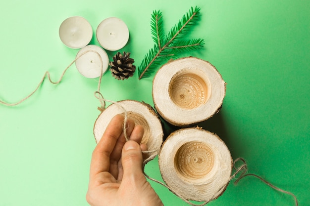 Bougeoir de noël bricolage fait de bûches de pin, de bougies, de corde artisanale, de branches de sapin et de cônes. les mains attachent et attachent la corde. instructions étape par étape à plat, étape 3.
