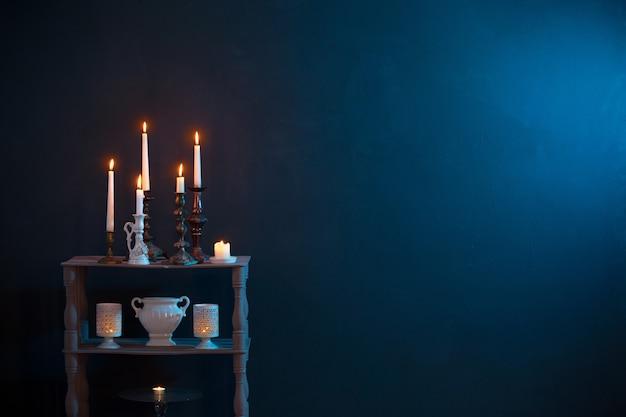Bougeoirs avec des bougies allumées sur fond bleu foncé