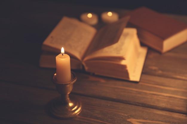 Bougie allumée et bible sur table en bois