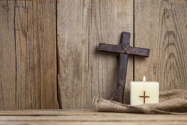 Bougie allumée et croix sur fond de bois