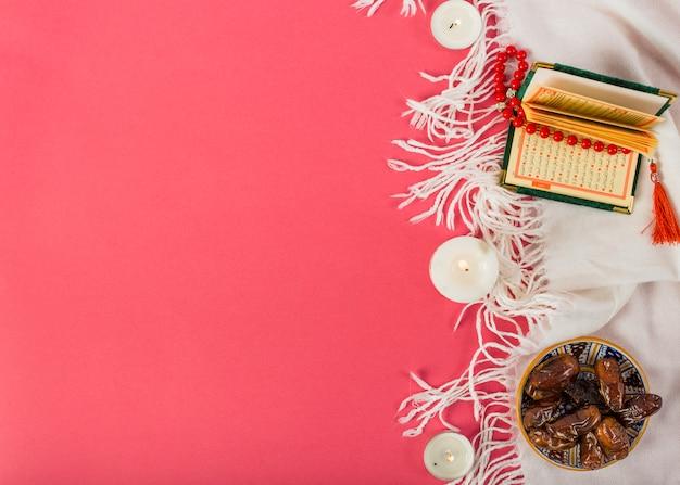 Bougie allumée avec des dates juteuses; saint kuran et perles sur châle blanc sur fond rouge