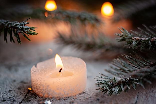 Bougie allumée et décoration de noël sur la neige avec des branches de pin sur un fond en bois blanc.