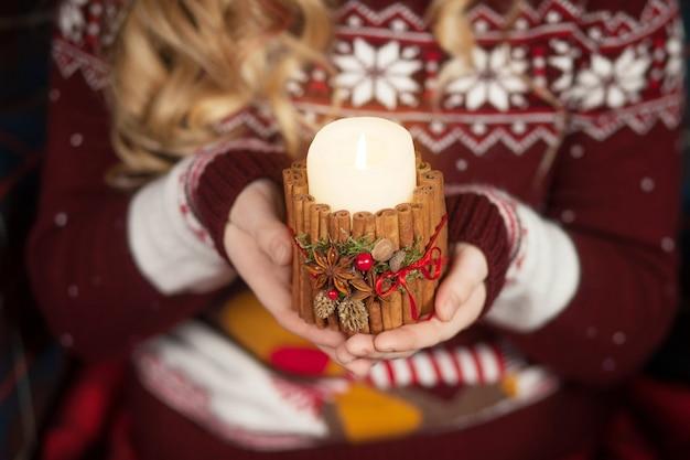 Bougie allumée entre les mains d'une fille. bougie de noël. décor de noël. mains de l'enfant tenant belle bougie avec feu