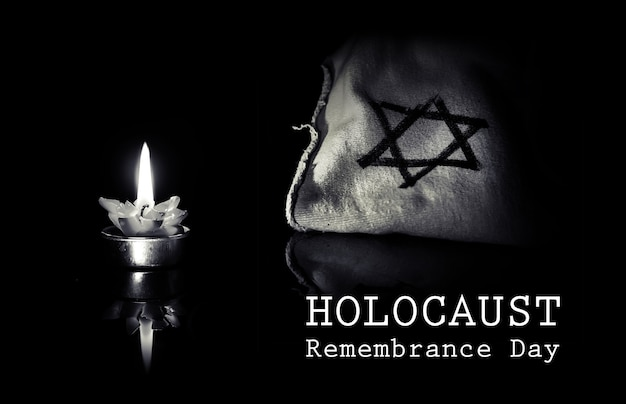 Bougie allumée et étoile de david sur fond noir, nous n'oublierons jamais, l'holocauste et l'héroïsme juifs. jour du souvenir de l'holocauste 27 janvier