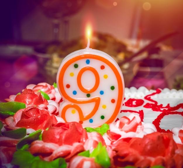 Bougie allumée en forme de gâteau numéro neuf décoré de motifs de fleurs et numéro neuf