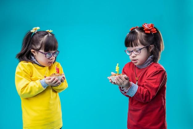 Bougie allumée à l'intérieur. mignonnes petites sœurs portant des tenues colorées et transportant des petits gâteaux en se tenant debout contre le mur bleu