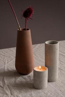 Bougie allumée, long verre en céramique blanche ou vase et pichet en argile brune avec deux fleurs sauvages sèches debout sur une nappe en lin sur un mur noir