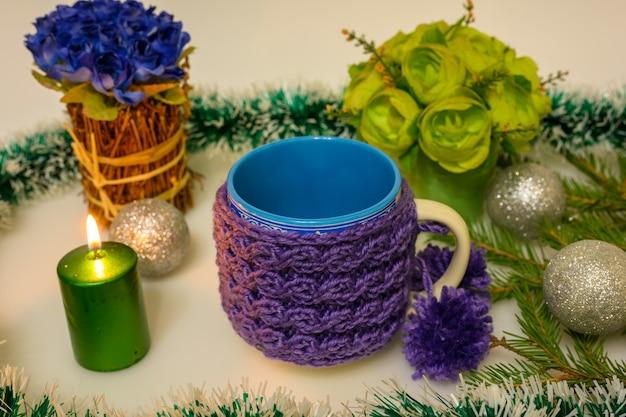 Bougie allumée et mug tricoté avec pompons.