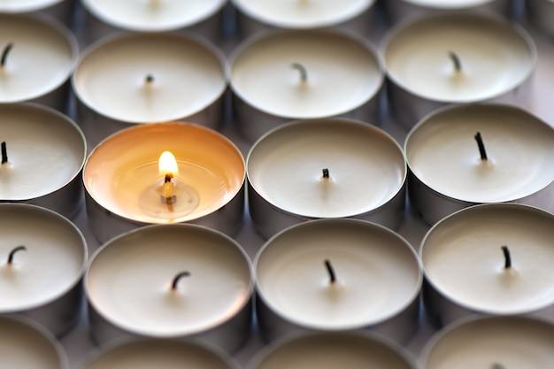 Une bougie allumée et de nombreuses bougies éteintes