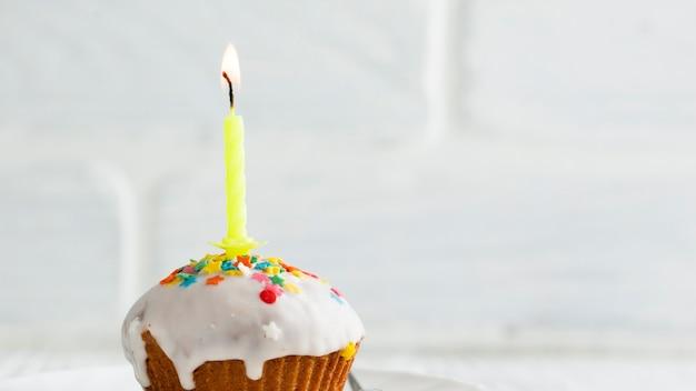 Bougie allumée sur petit gâteau avec glaçure blanche