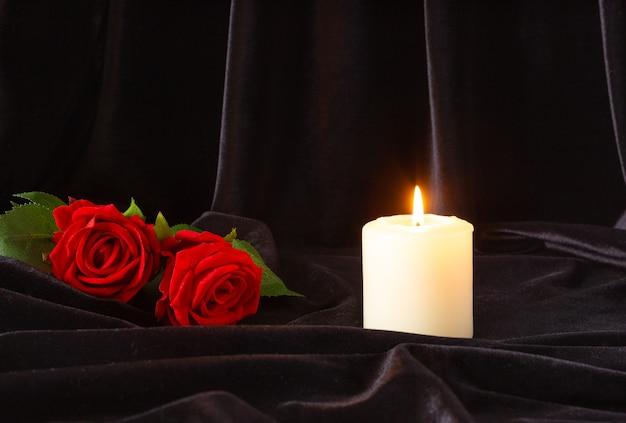 Une bougie allumée et une rose rouge sur fond noir