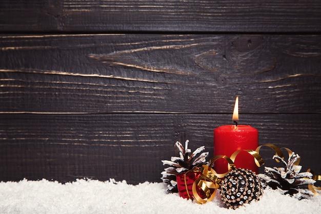 Bougie allumée rouge avec une planche en bois rustique noire