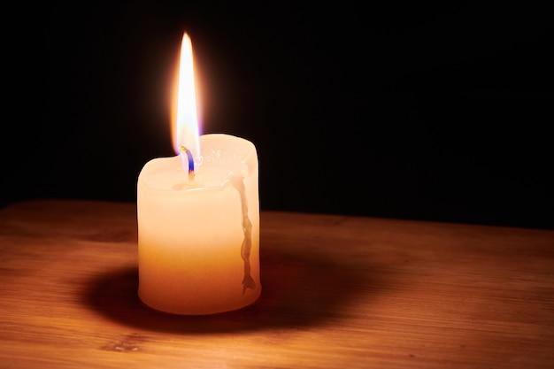 Bougie allumée sur la table dans l'obscurité de la nuit. flamme de l'espoir et de la mémoire.
