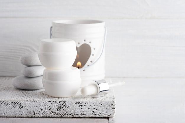 Bougie aromatique allumée blanche sur table rustique. arrangement de spa avec produit de beauté dans un style monochrome