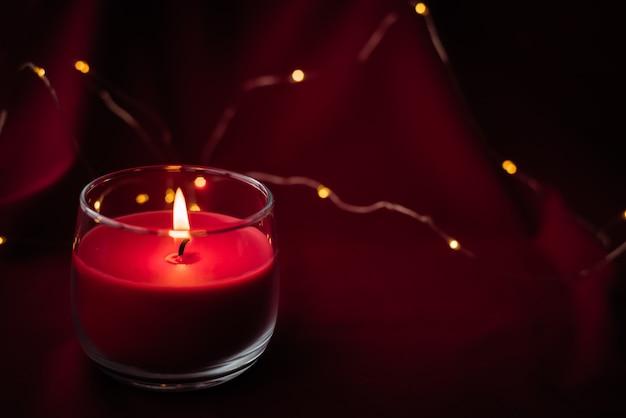 Bougie d'arôme rouge floue brûle et se dresse sur un fond rouge avec des lumières de guirlandes.