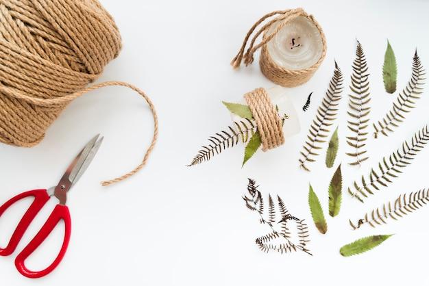 Bougie attachée avec ficelle et feuilles sur fond blanc
