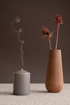Bougie basse grise soufflée avec de la fumée dessus et longue cruche en argile brune étroite ou vase avec deux fleurs sauvages sur mur noir