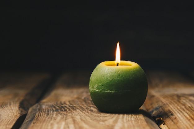 Une bougie blanche avec un fond sombre - dans un chandelier en bois.