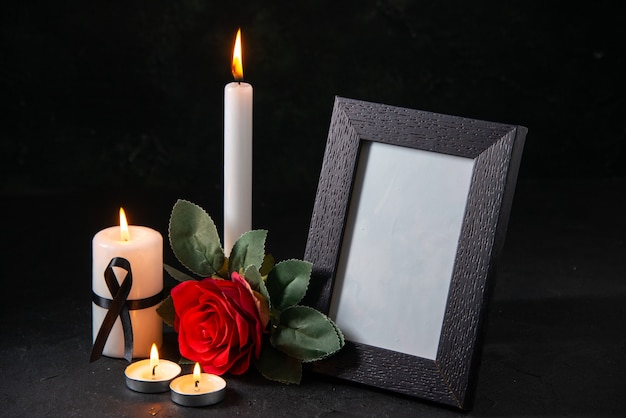 Bougie blanche vue de face avec cadre photo et fleur sur la surface sombre