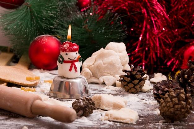 Une bougie de bonhomme de neige brûle sur la table, processus de fabrication de biscuits de noël