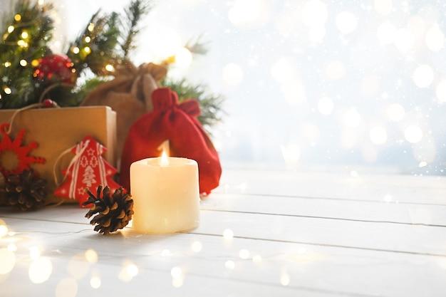 Bougie et cadeaux de joyeux noël sur la table blanche à côté des branches de l'arbre de noël et des lumières