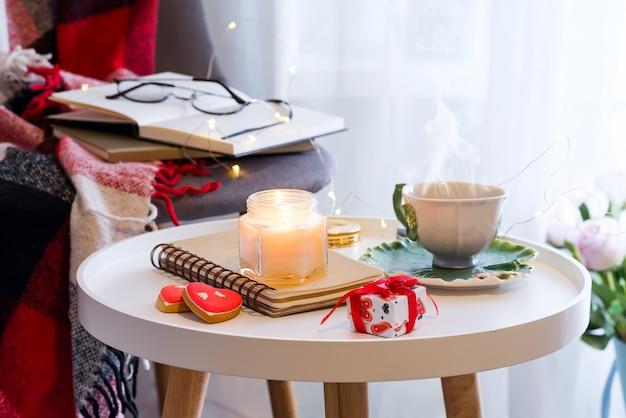Une bougie avec un cahier sur une table avec des roses roses dans une boîte près d'une fenêtre avec une chaise, un plaid et un livre